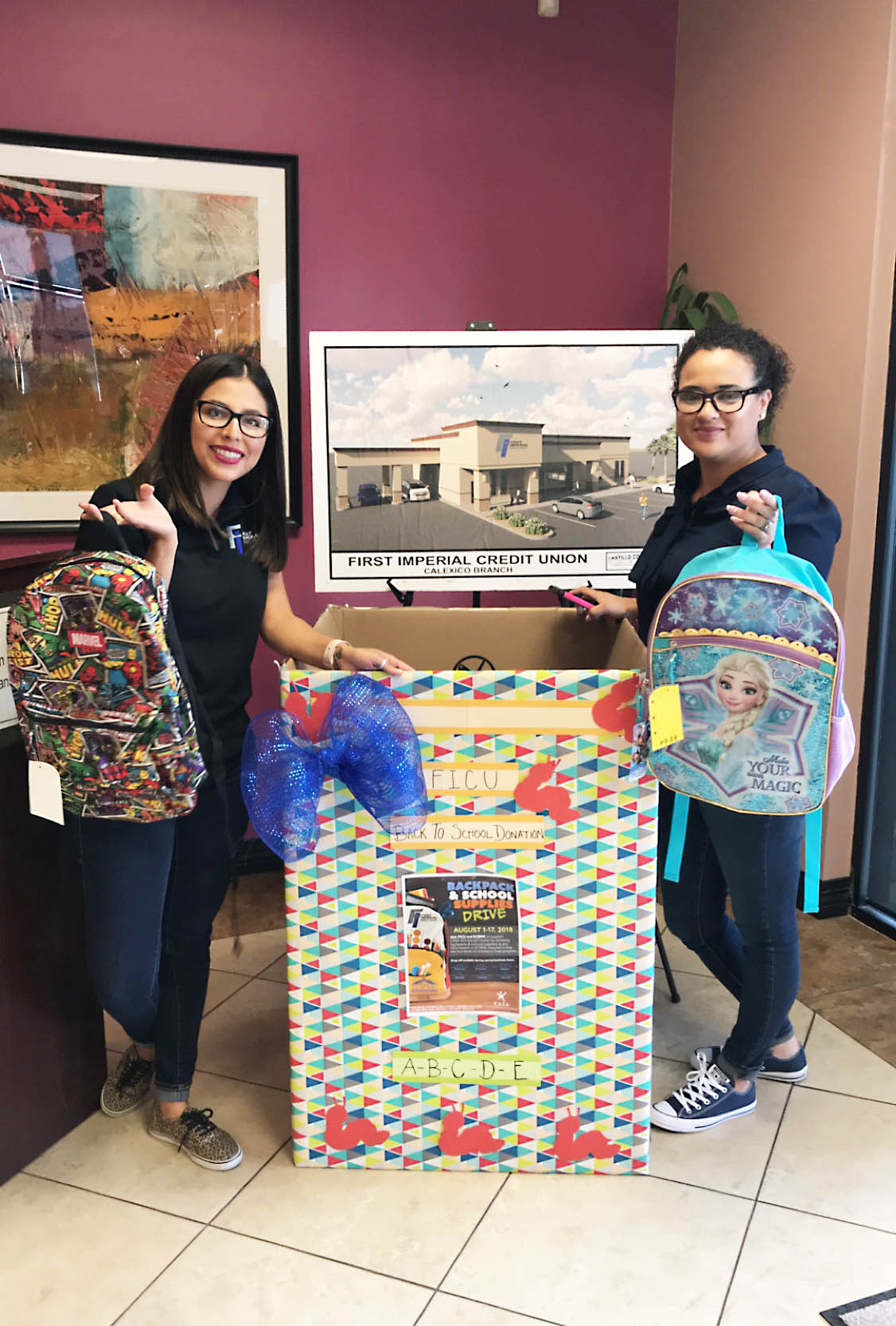FICU staff at the Calexico Branch hold up their first backpack donations.